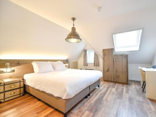 A bed or beds in a room at Brasserie-Hotel Antje van de Statie