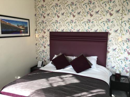 A bed or beds in a room at Queenswood Hotel