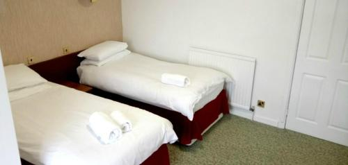 A bed or beds in a room at Traquair Arms Hotel