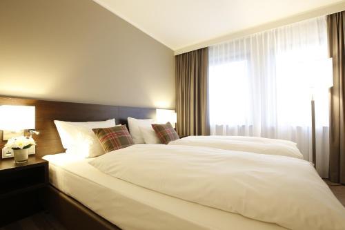 Ein Bett oder Betten in einem Zimmer der Unterkunft Parkhotel Wittekindshof