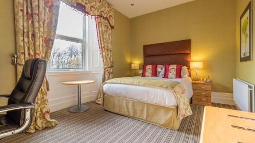 A bed or beds in a room at Hunday Manor Country House Hotel