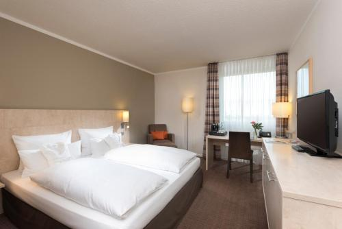 A bed or beds in a room at Mercure Hotel Düsseldorf Süd