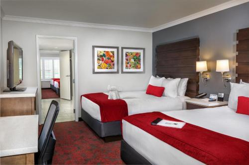 A bed or beds in a room at Desert Palms Hotel & Suites Anaheim Resort