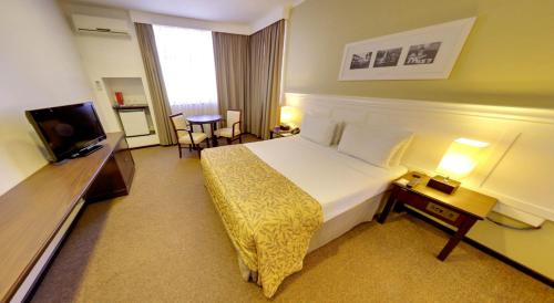 A bed or beds in a room at Marques Plaza Hotel