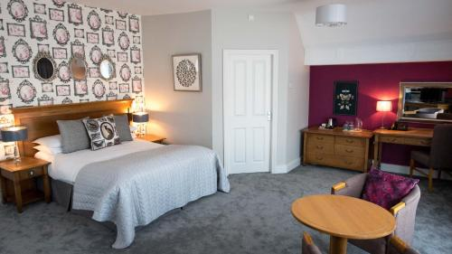 A bed or beds in a room at The Coach House Inn