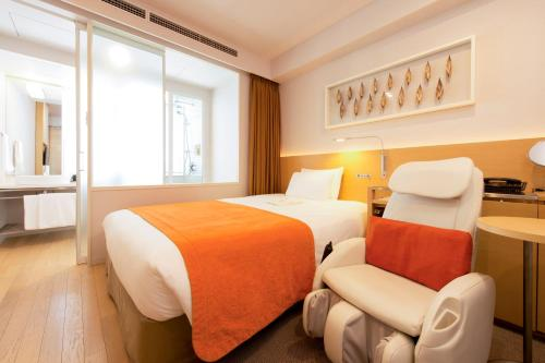 A bed or beds in a room at remm Hibiya