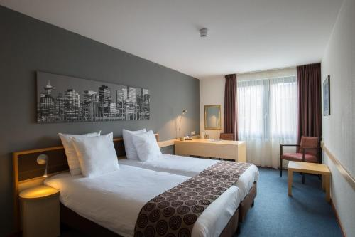 A bed or beds in a room at Hotel Rotterdam