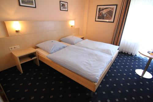 A bed or beds in a room at Hotel Am Tiergarten