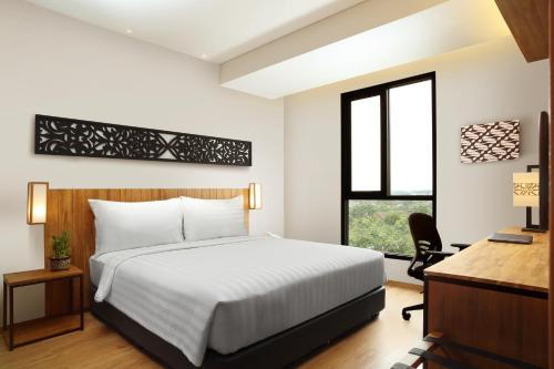 A bed or beds in a room at BATIQA Hotel Pekanbaru