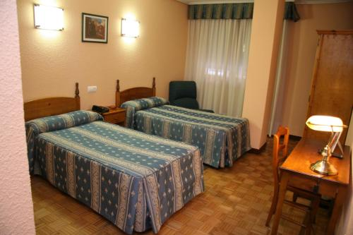 A bed or beds in a room at Hotel San Glorio