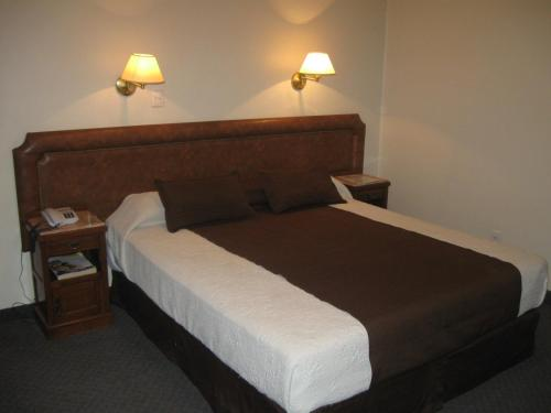A bed or beds in a room at Hotel Muñiz