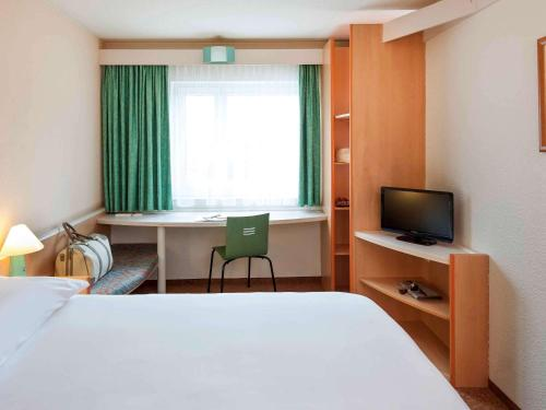A bed or beds in a room at ibis Hotel Dortmund City