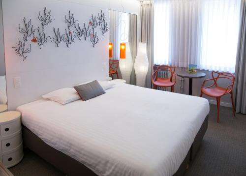 A bed or beds in a room at Logis Hotel Glenmore