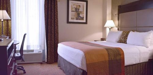 A bed or beds in a room at Hamilton Plaza Hotel and Conference Center