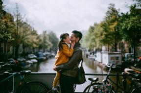 A father and daughter hugging and smiling while standing on a bridge over a canal.