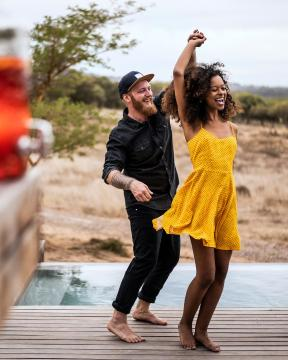 Two people smiling and dancing barefoot near a swimming pool.