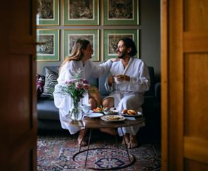 Two people in bathrobes smiling while enjoying breakfast in their hotel room.