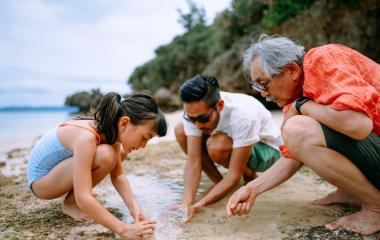 Three people on a beach collecting water and sand in a cup.