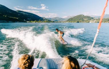 A person wakeboarding on a lake while two others watch from a boat.